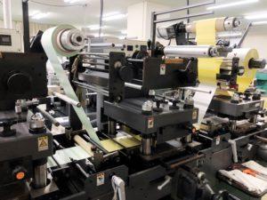 両面テープへ印刷物を当寸で精密貼合。